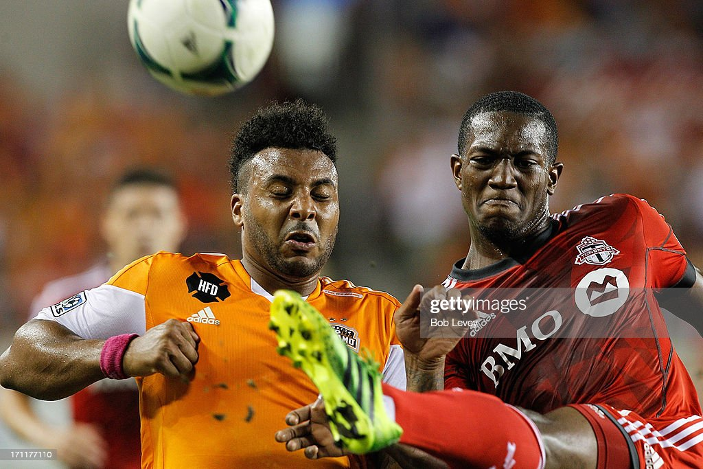 Doneil Henry #4 of Toronto FC gets his foot up in the face of Giles Barnes #23 of Houston Dynamo as he clears the ball in the second half at BBVA Compass Stadium on June 22, 2013 in Houston, Texas.
