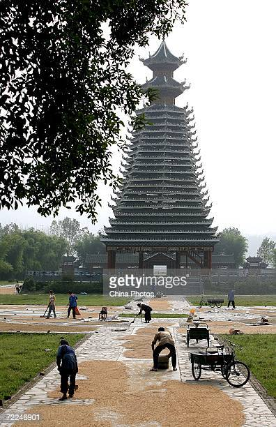 Dong ethnic minority people work in front of a Drum Tower at the Sanbao Dong Village on October 19 2006 in Rongjiang County of Qiandongnan Miao and...