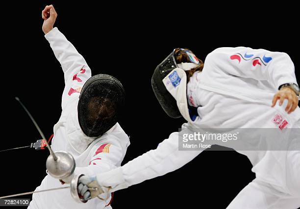 Dong Guotao of China competes with Kim Seung Gu of Republic of Korea in the Men's Team Epee Gold Medal match during the 15th Asian Games Doha 2006 at...