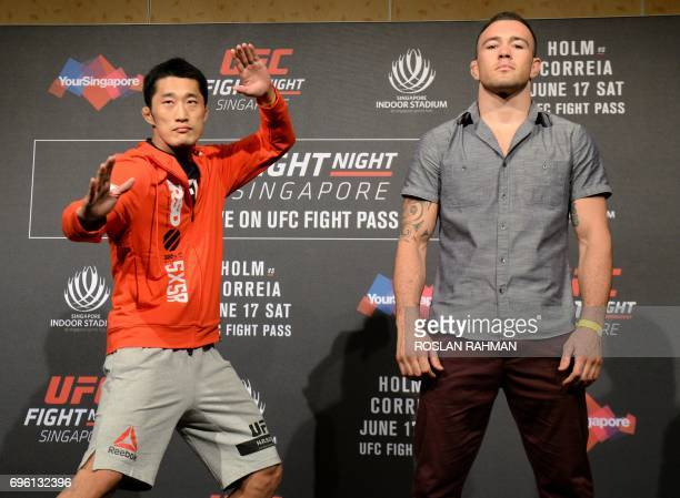 Dong Hyun Kim of South Korea and Colby Covington of the US pose for photographers during the UFC Fight Night media event in Singapore on June 15 2017...
