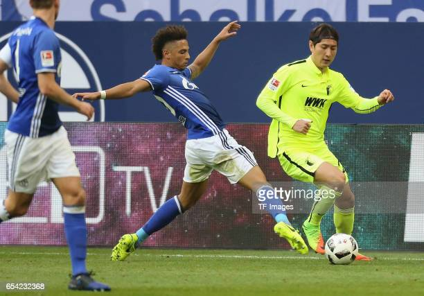 DongWon Ji of Augsburg and Thilo Kehrer of Schalke battle for the ball during the Bundesliga match between FC Schalke 04 and FC Augsburg at...