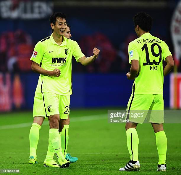 DongWon Ji of Augsburg celebrates scoring his goal with JaCheol Kool during the Bundesliga match between RB Leipzig and FC Augsburg at Red Bull Arena...