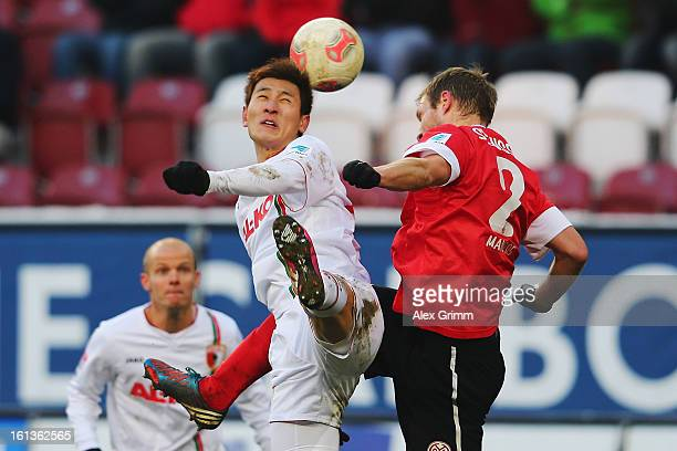 DongWon Ji of Augsburg is challenged by Bo Svensson of Mainz during the Bundesliga match between FC Augsburg and 1 FSV Mainz 05 at SGL Arena on...