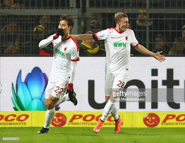 DongWon Ji of FC Augsburg celebrates scoring the opening goal with Georg Teigl during the Bundesliga match between Borussia Dortmund and FC Augsburg...