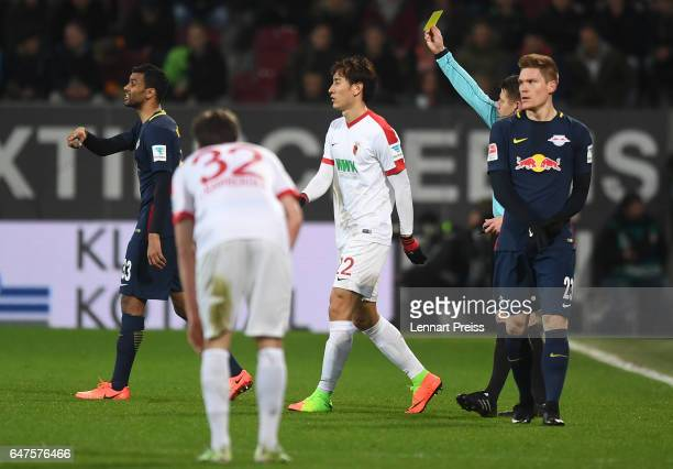 DongWon Ji of FC Augsburg is shown the yellow card by referee Patrick Ittrich during the Bundesliga match between FC Augsburg and RB Leipzig at WWK...