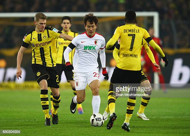 DongWon Ji of FC Augsburg takes on Ousmane Dembele of Borussia Dortmund during the Bundesliga match between Borussia Dortmund and FC Augsburg at...