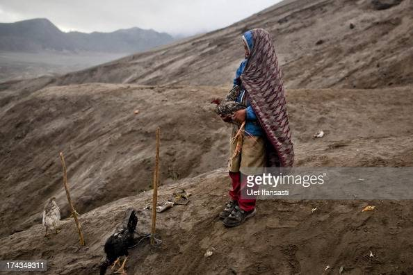 Doni holds a chicken result of catch thrown by Hindu worshippers at foot of Mount Bromo during the Yadnya Kasada Festival at crater of Mount Bromo on...