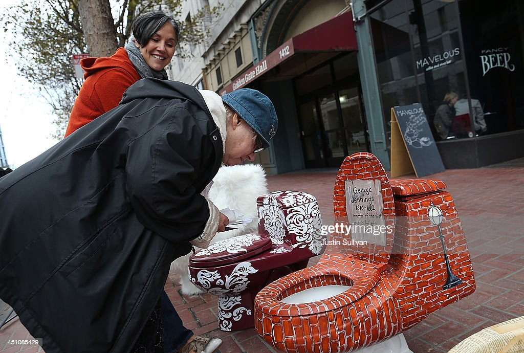 Doniece Sandoval (L) shows a passerby a decorated toilet that is part of a public art installation titled 'C'mon, give a shit' to mark World Toilet Day and to bring attention to a project to convert retired MUNI buses into mobile showers for the homeless on November 21, 2013 in San Francisco, California. Lava Mae founder Doniece Sandoval coordinated the public art installation of decorated toilets to raise awareness about the millions of people around the world who do not have access to clean and private toilets. The installation also promotes the nonprofit Lava Mae's project to convert old San Francisco municipal buses into mobile showers for homeless people in the city.