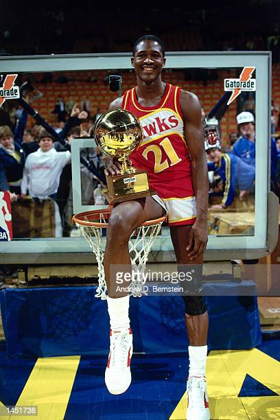Doninique Wilkins of the Atlanta Hawks poses on top of the basket with the Slam Dunk Champion Trophy after wining the contest during the NBA All Star...