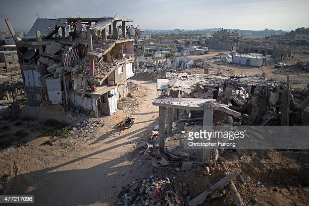 A donkey and cart move through the dust and rubble of bombed homes that still wait to be demolished or rebuilt on June 15 Gaza City Gaza The...
