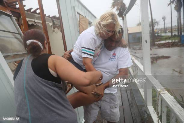 Donna Raney is helped out of the window by Lee Guerrero and Daisy Graham after Hurricane Harvey destroyed her apartment on August 26 2017 in Rockport...