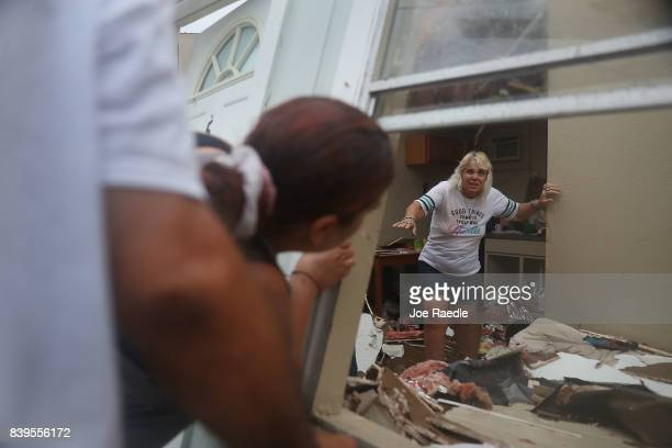 Donna Raney makes her way out of the wreckage of her home as Daisy Graham tells her she will help her out of the window after Hurricane Harvey...