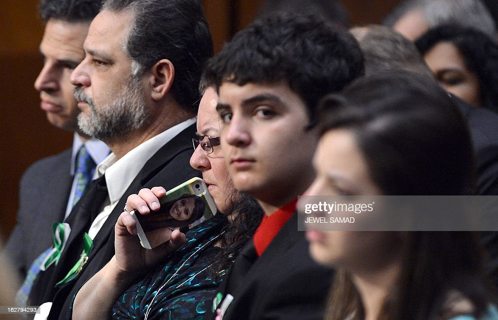 Donna Soto (C), mother of slain Sandy Hook Elementary School teacher Victoria Soto, holds a cell phone with her daughter's picture on it while attending Senate Judiciary Committee hearing on 'The Assault Weapons Ban of 2013' at the Hart Senate Office Building in Washington, DC, on February 27, 2013. AFP PHOTO/Jewel Samad