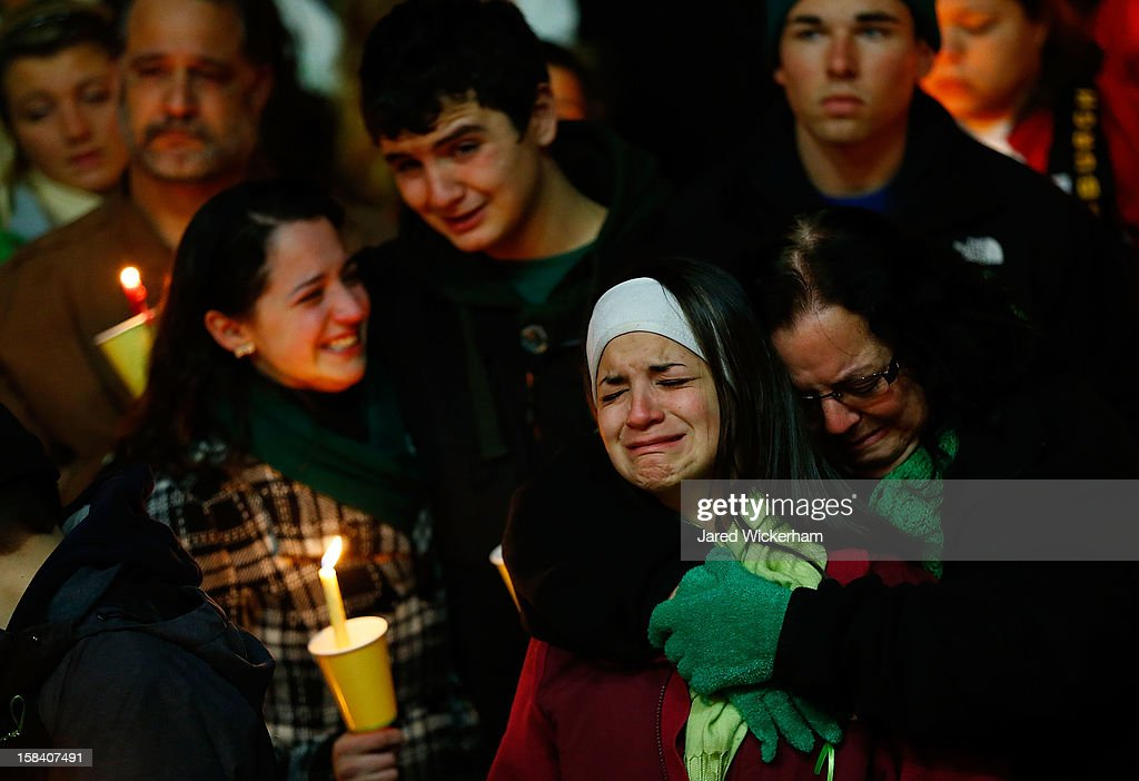 Donna Soto (R), mother of Victoria Soto, the first-grade teacher at Sandy Hook Elementary School who was shot and killed while protecting her students, hugs her daughter Karly (second from right) while mourning their loss with Victoria's other two siblings, Jillian (far left) and Matthew Soto (second from left), at a candlelight vigil at Stratford High School on December 15, 2012 in Stratford, Connecticut. Twenty-six people were shot dead, including twenty children, after a gunman identified as Adam Lanza opened fire in the school. Lanza also reportedly had committed suicide at the scene. A 28th person, believed to be Nancy Lanza was found dead in a house in town, was also believed to have been shot by Adam Lanza.