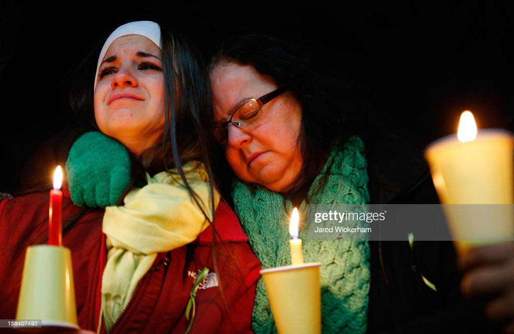 Donna Soto (R), mother of Victoria Soto, the first-grade teacher at Sandy Hook Elementary School who was shot and killed while protecting her students, hugs her daughter Karly while mourning their loss at a candlelight vigil in honor of Victoria at Stratford High School on December 15, 2012 in Stratford, Connecticut. Twenty-six people were shot dead, including twenty children, after a gunman identified as Adam Lanza opened fire in the school. Lanza also reportedly had committed suicide at the scene. A 28th person, believed to be Nancy Lanza was found dead in a house in town, was also believed to have been shot by Adam Lanza.