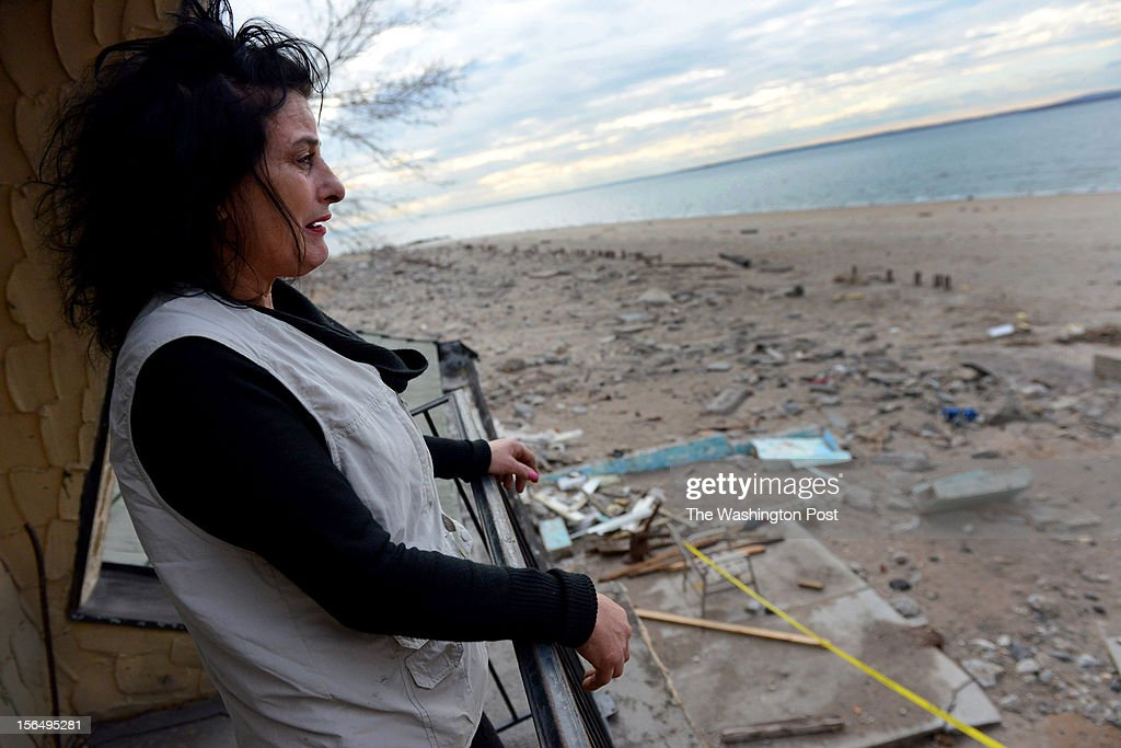 Donna Zurlo, cries on the porch of her beachfront home that is without power, water and has incurred heavy damage in community of Seagate in Brooklyn, NY on November 13, 2012. The swimming pool is now in the living room and cement deck facing the water is about all that's left standing in the yard. Seagate, a beachside community along the lower shoreline of Brooklyn still suffers from power outages from Hurricane Sandy. The city has brought in some lighting to an otherwise dark neighborhood. Zurlo's friend who owns the house, has been under such duress from the hurricane damaged that his family is handling his affairs. A claim with FEMA was filed by the his family for damages with Zurlo's name on it and she hopes she can recover some of her belongings which were lost. 'I've lost everything, I'm only 53, and I don't even have a claim number.' She's lived in this house with her friend for over 20 years.