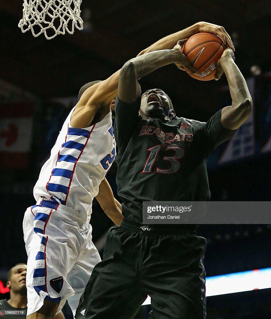 Donnavan Kirk #23 of the DePaul Blue Demons blocks a shot by Cheikh Mbodj of the Cincinnati Bearscats at Allstate Arena on January 15, 2013 in Rosemont, Illinois.