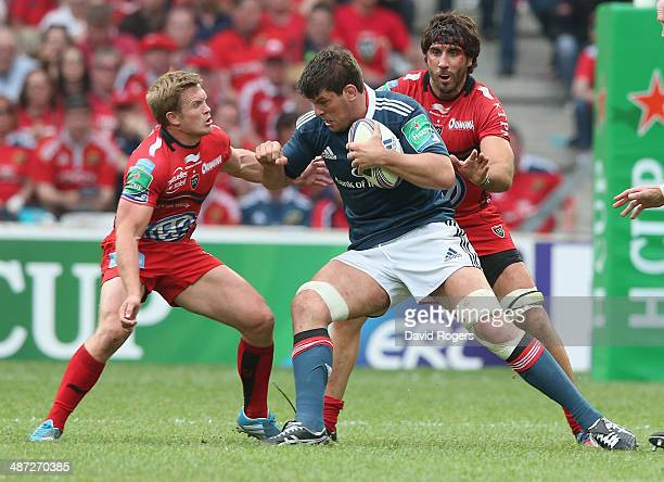Donncha O'Callaghan of Munster is tackled by Michael Claassens and Juan FernandezLobbe during the Heineken Cup semi final match between Toulon and...