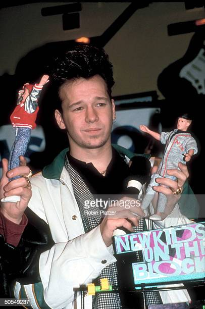 Donnie Wahlberg of the rock group New Kids on the Block holding up NKOTB merchandise