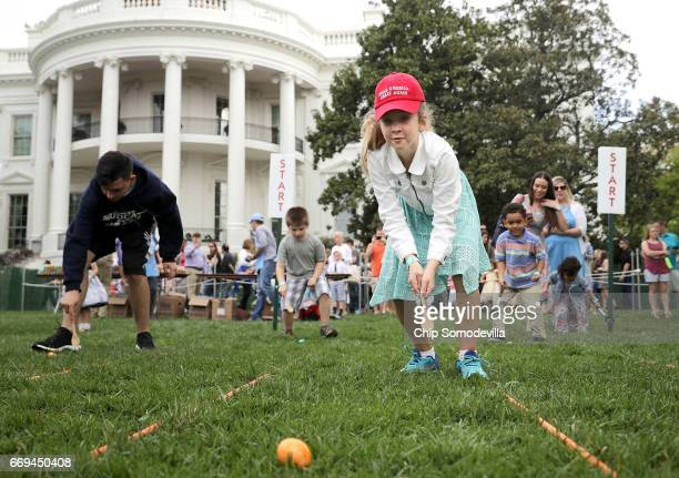 Donning a 'Make America Great Again' hat 10yearold Olivia Smith of Red Hook NY rolls an colored egg down the White House South Lawn during the 139th...
