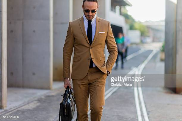 Donny Galella wearing a beige suit and black tie and weekender bag outside Ginger Smart at MercedesBenz Fashion Week Resort 17 Collections at...