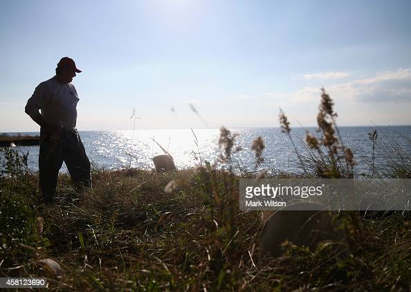 Donny Willey stands near graves that were once several yards from the waters edge are now exposed and releasing human remains by the eroding waters...