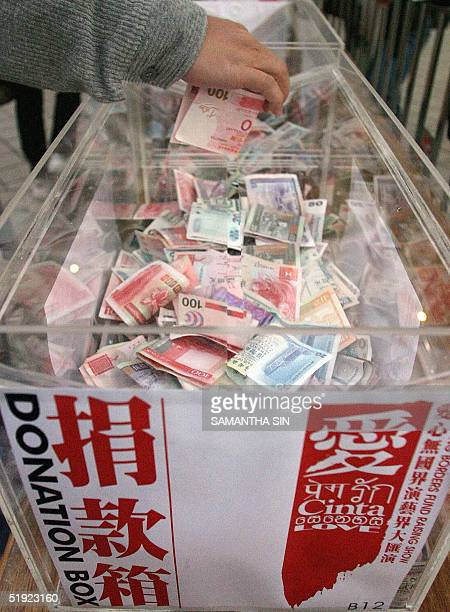 A donor puts money into a donation box at a charity concert for tsunami victims at Hong Kong Stadium 07 January 2005 Morn than 100 celebrities from...