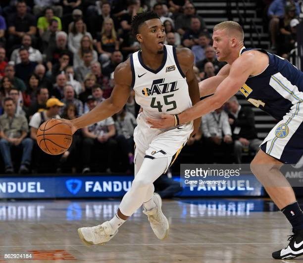 Donovan Mitchell of the Utah Jazz controls the ball in the first half while being defended by Mason Plumlee of the Denver Nuggets at Vivint Smart...