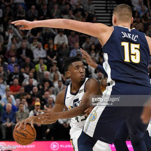 Donovan Mitchell of the Utah Jazz controls the ball while being defended by Nikola Jokic of the Denver Nuggets in the first half at Vivint Smart Home...