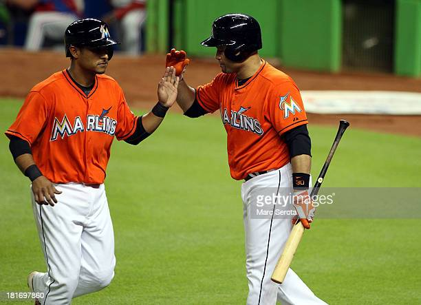 Donovan Solano and Placido Poanco of the Miami Marlins celebrate a run against the Philadelphia Phillies at Marlins Park on September 23 2013 in...