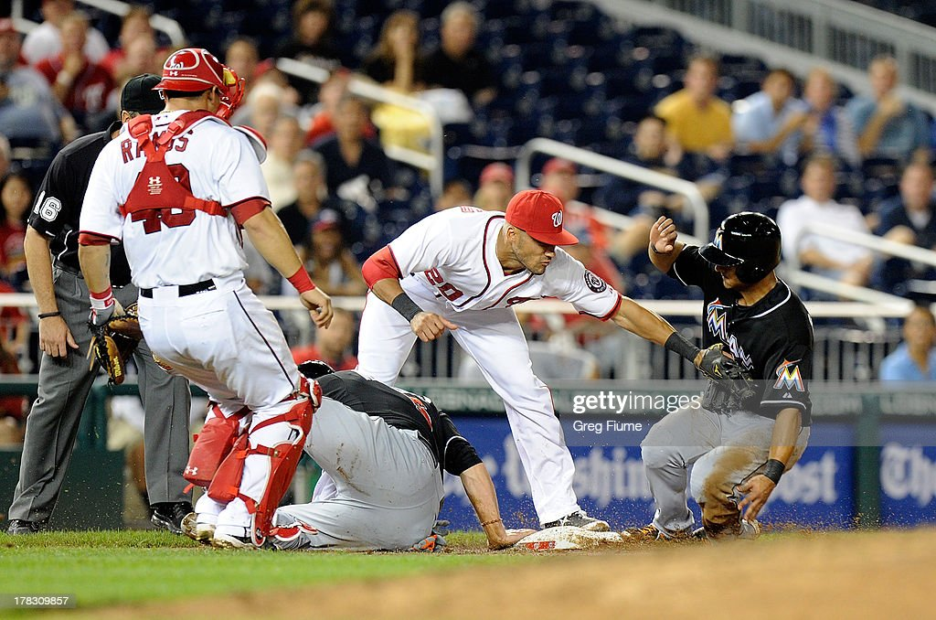 Donovan Solano #17 of the Miami Marlins is safe at third base after Logan Morrison #5 was tagged out in the sixth inning by <a gi-track='captionPersonalityLinkClicked' href=/galleries/search?phrase=Ian+Desmond&family=editorial&specificpeople=835572 ng-click='$event.stopPropagation()'>Ian Desmond</a> #20 of the Washington Nationals at Nationals Park on August 28, 2013 in Washington, DC.
