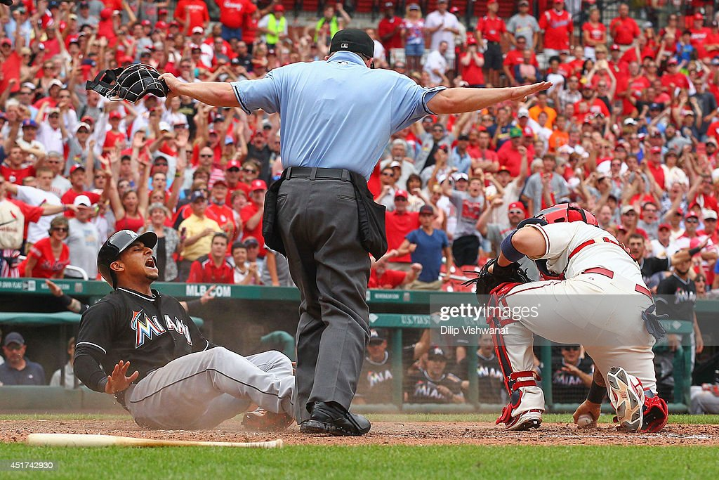 Donovan Solano #17 of the Miami Marlins reacts after scoring the game-tying run against <a gi-track='captionPersonalityLinkClicked' href=/galleries/search?phrase=Yadier+Molina&family=editorial&specificpeople=172002 ng-click='$event.stopPropagation()'>Yadier Molina</a> #4 of the St. Louis Cardinals at Busch Stadium on July 5, 2014 in St. Louis, Missouri. The Marlins beat the Cardinal 6-5.