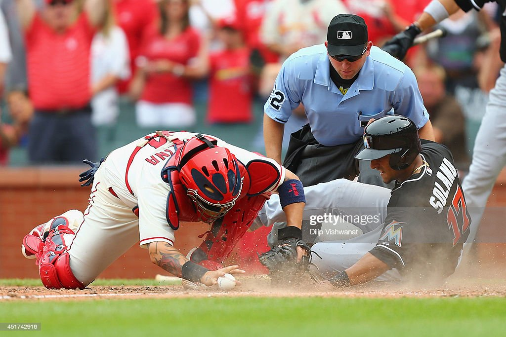 Donovan Solano #17 of the Miami Marlins scores the game-tying run against <a gi-track='captionPersonalityLinkClicked' href=/galleries/search?phrase=Yadier+Molina&family=editorial&specificpeople=172002 ng-click='$event.stopPropagation()'>Yadier Molina</a> #4 of the St. Louis Cardinals as umpire Clint Fagan #82 looks to make the call in the ninth inning at Busch Stadium on July 5, 2014 in St. Louis, Missouri. The Marlins beat the Cardinal 6-5.