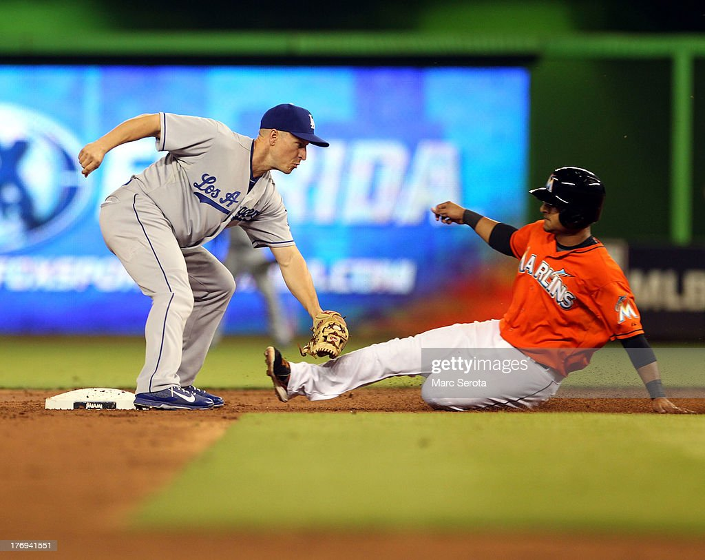 Donovan Solano #17 of the Miami Marlins slides into a double play by second baseman <a gi-track='captionPersonalityLinkClicked' href=/galleries/search?phrase=Mark+Ellis+-+Baseball+Player&family=editorial&specificpeople=213759 ng-click='$event.stopPropagation()'>Mark Ellis</a> #14 of the Los Angeles Dodgers at Marlins Park on August 19, 2013 in Miami, Florida.