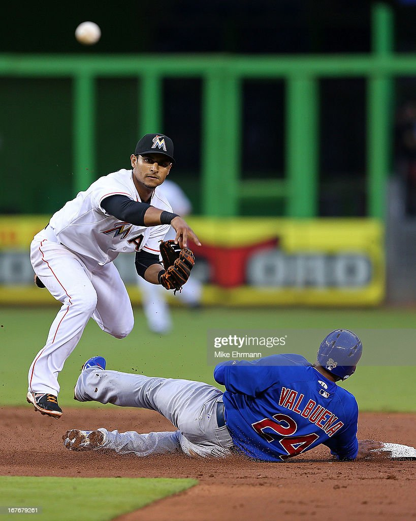 Donovan Solano #17 of the Miami Marlins turns a double play as Luis Valbuena #24 of the Chicago Cubs slides into second during a game at Marlins Park on April 27, 2013 in Miami, Florida.