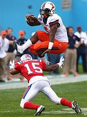 Donovonn Young of the Illinois Fighting Illini jumps over the tackle of Bryson Abraham of the Louisiana Tech Bulldogs during the Zaxby's Heart of...