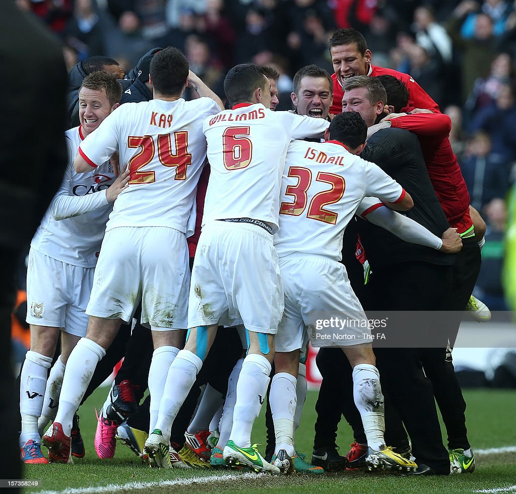 MK Dons players and staff celebrate after Jon Otsemober scored their team's second goal during the FA Cup with Budweiser Second Round match between MK Dons and AFC Wimbledon at StadiumMK on December 2, 2012 in Milton Keynes, England.