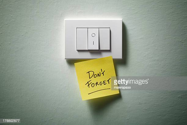 Don't forget. Light switch with yellow sticky note.