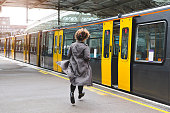 Rear view of a woman running to catch the train before it leaves the station without her.