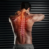 Studio shot of a muscular young man rubbing his neck with his spinal column showing through cgi