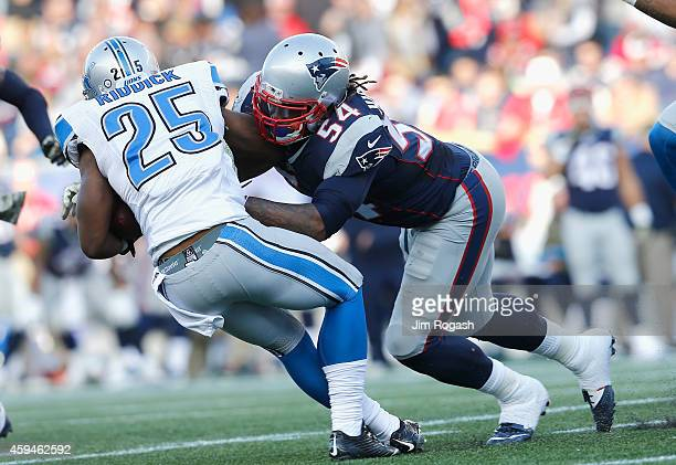 Dont'a Hightower of the New England Patriots tackles Theo Riddick of the Detroit Lions during the second quarter at Gillette Stadium on November 23...