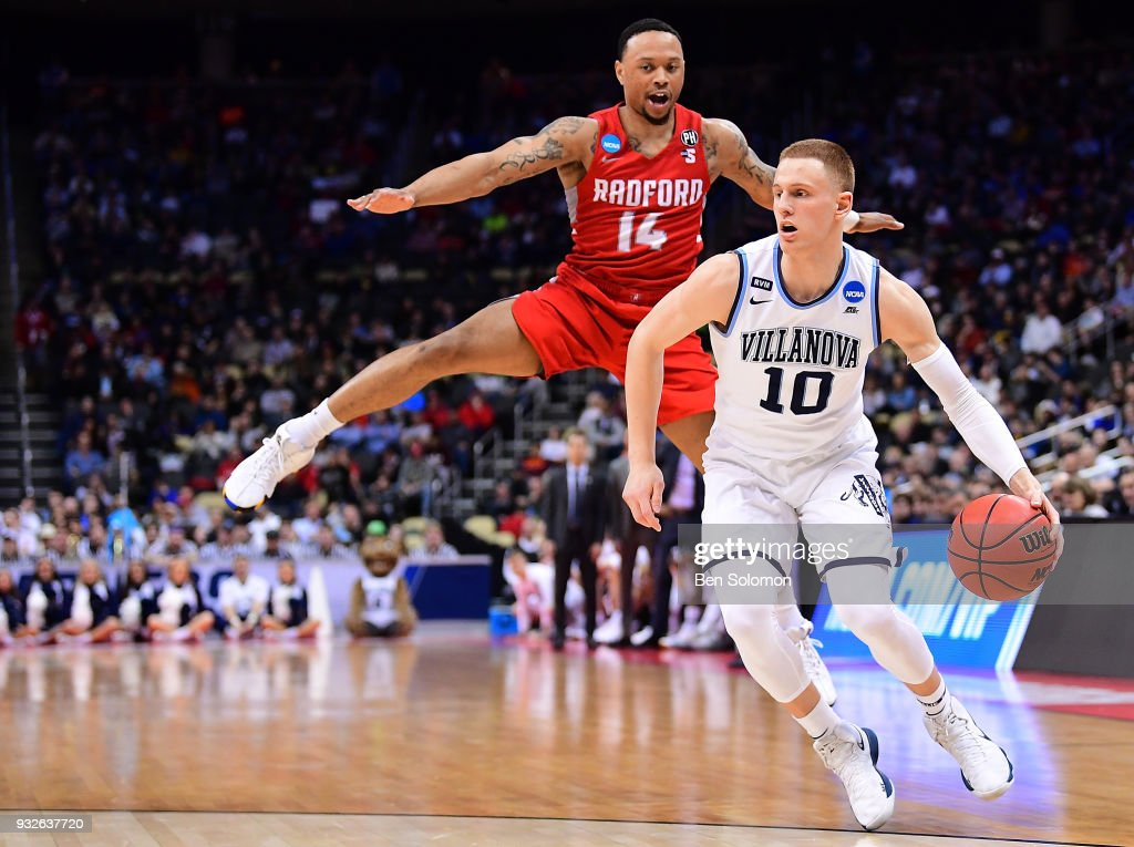 Donte DiVincenzo #10 of the Villanova Wildcats dribbles as Justin Cousin #14 of the Radford Highlanders goes airborne in the first half during the first round of the 2018 NCAA Men's Basketball Tournament held at PPG Paints Arena on March 15, 2018 in Pittsburgh, Pennsylvania.
