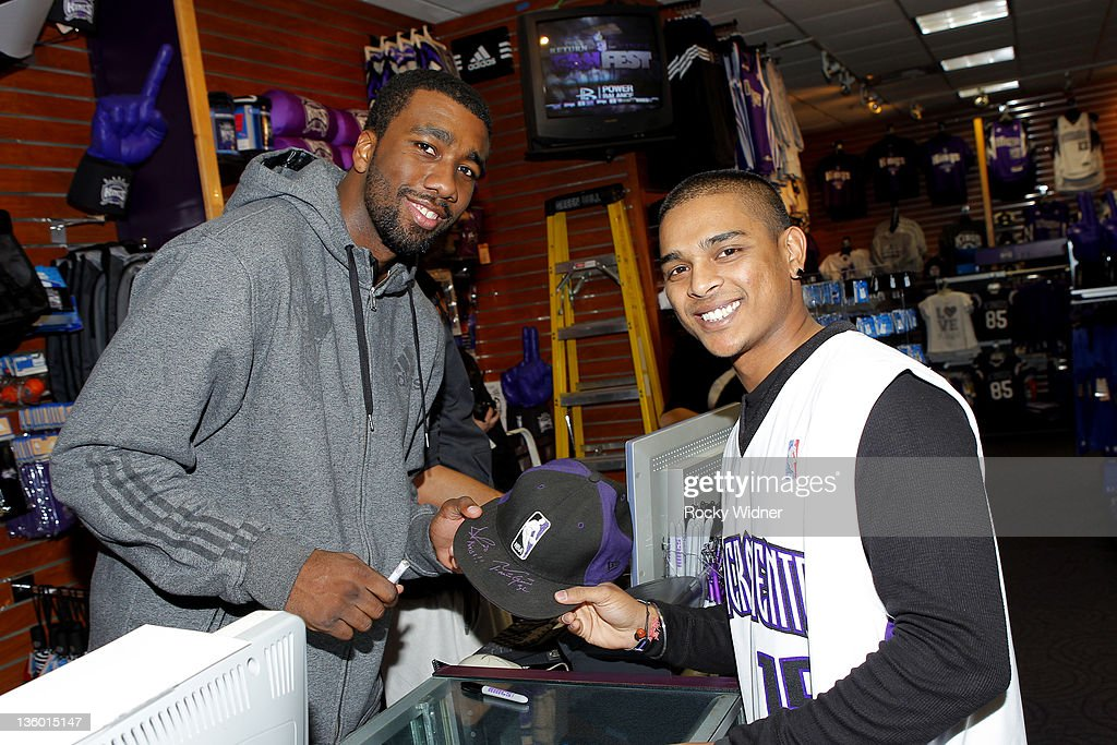 Donte Greene #20 (L) of the Sacramento Kings poses for a photo with a fan on December 15, 2011 at Power Balance Pavilion in Sacramento, California.