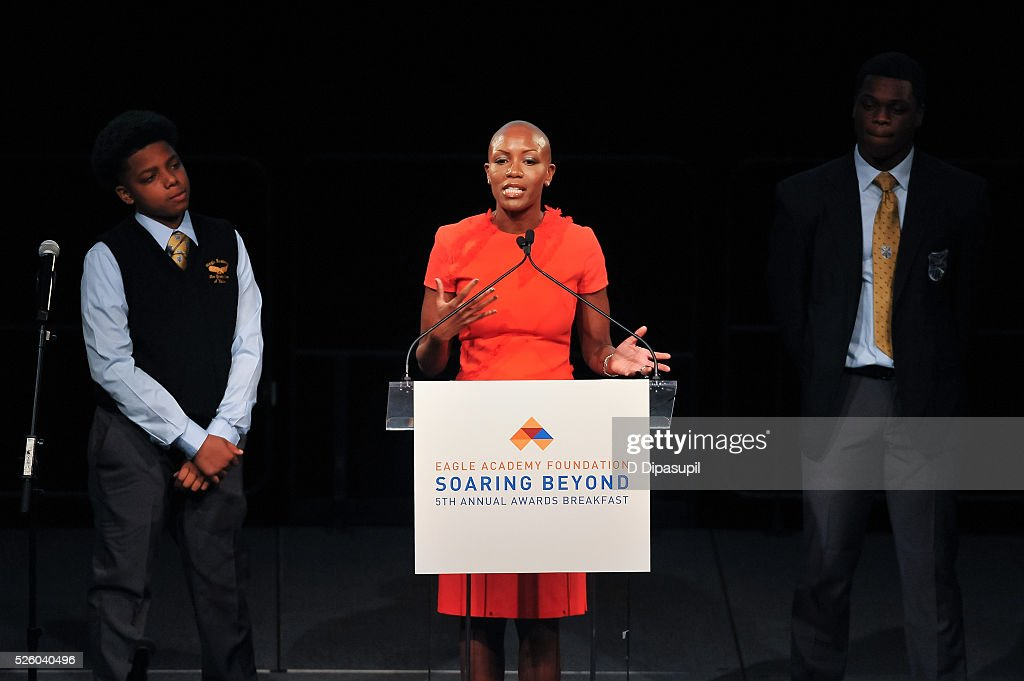 Donte Jones (L) and Jamal Trotman (R) look on as News Corp chief human resources officer Keisha Smith-Jeremie speaks onstage during the 2016 Eagle Academy Foundation Fundraising Breakfast at Gotham Hall on April 29, 2016 in New York City.
