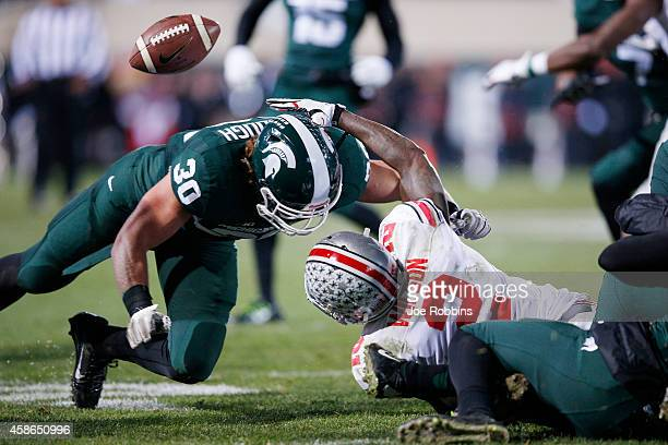 Dontre Wilson of the Ohio State Buckeyes fumbles the ball on a kick return after being hit by Riley Bullough of the Michigan State Spartans in the...