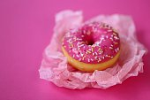 Donut. pink donut on a light pink crumpled paper on a bright fuchsia background. Appetizing dessert