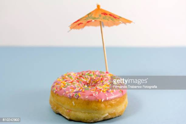 Donut with umbrella on the beach. Summer food