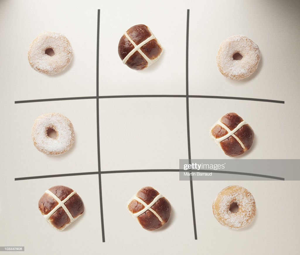 Donuts and hot cross buns on tic-tac-toe grid : Stock Photo