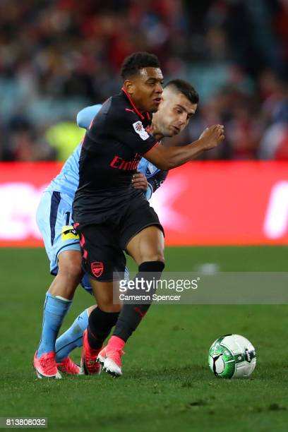 Donyell Malen of Arsenal is is tackled by Christopher Zuvela of Sydney FC during the match between Sydney FC and Arsenal FC at ANZ Stadium on July 13...