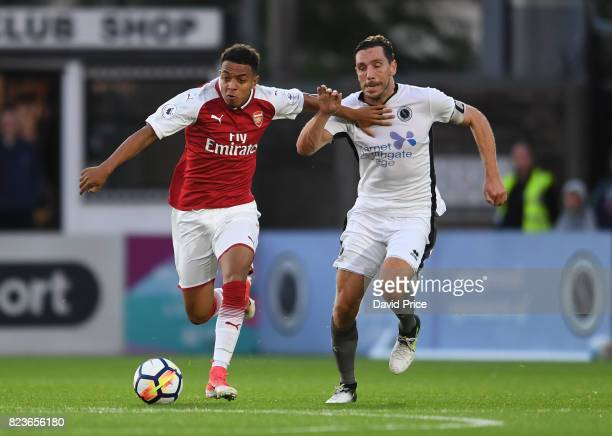 Donyell Malen of Arsenal takes on Tom Champion of Boreham Wood during the match between Boreham Wood and Arsenal XI at Meadow Park on July 27 2017 in...